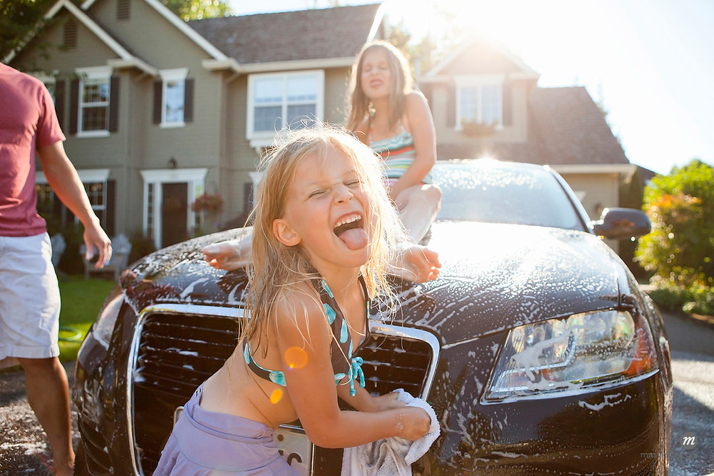 A family washes their car in the driveway of their home on a sunny summer afternoon in Portland, Oregon, USA © Ty Milford / Masterfile