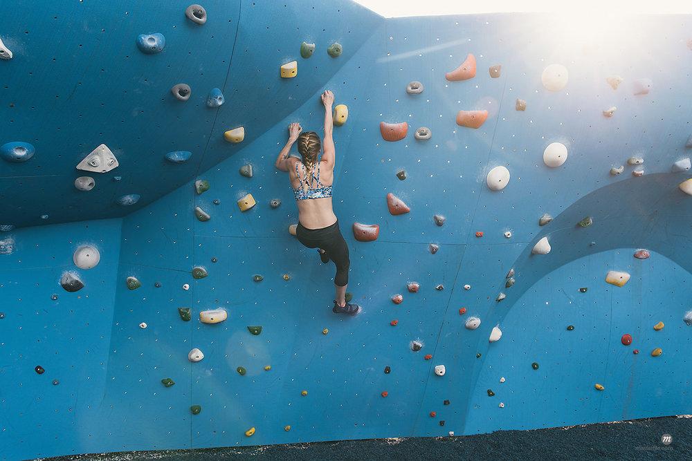 Young woman on climbing wall, Brooklyn Bridge Park, Brooklyn, NY, USA © Masterfile
