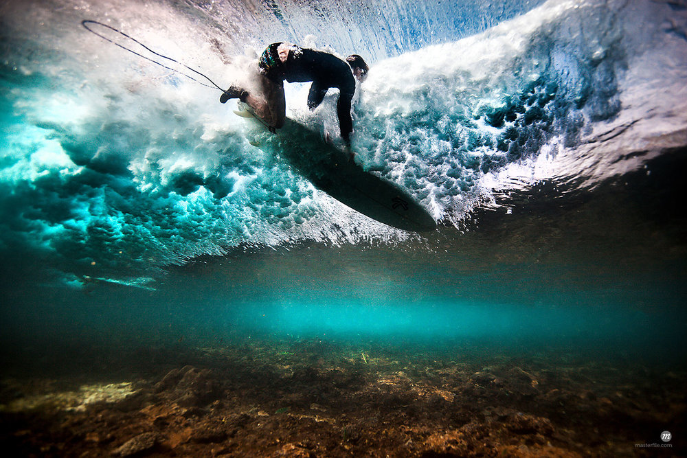 Underwater view of surfer falling through water after catching a wave on a shallow reef in Bali, Indonesia © Masterfile