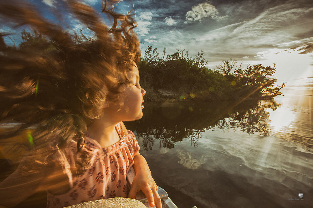Young girl enjoying cruise on river, eyes closed basking in sunlight, Homosassa, Florida, USA © Masterfile