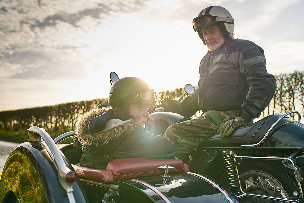 Senior man and grandson looking back from motorcycle and sidecar  © Masterfile