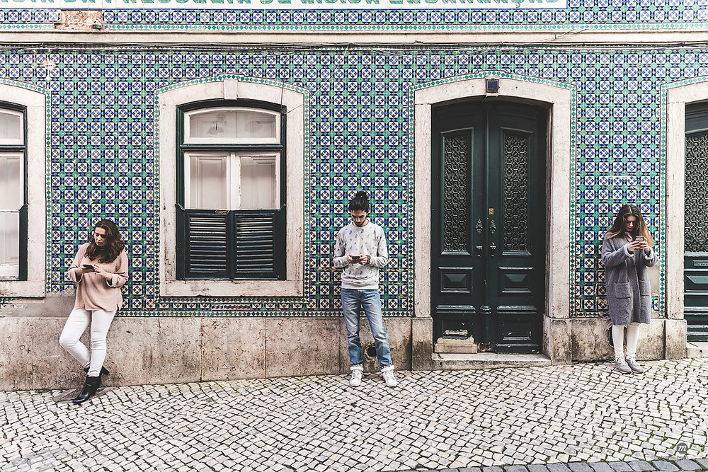 Young adults in Lisbon, Portugal standing in front of mosaic tile building looking at smartphones  © Masterfile