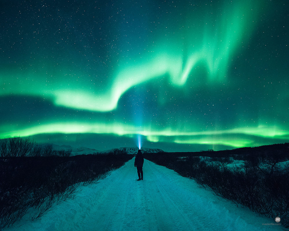 Mature man standing, watching Northern Lights, Thingvellir, Iceland © Masterfile