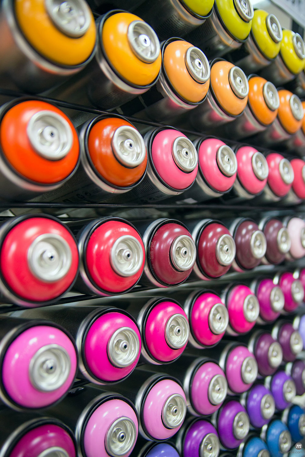 Colorful cans of spray paint in rows on a shelf © mila103 / Masterfile