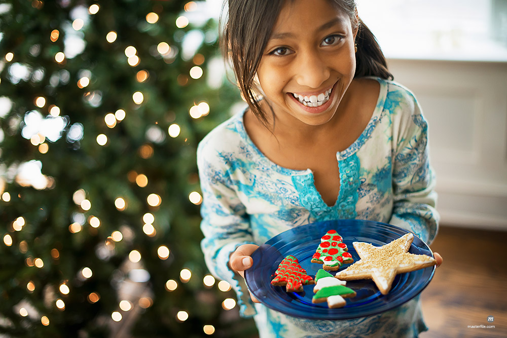 A young girl holding a plate of organic decorated Christmas cookies  © Masterfile