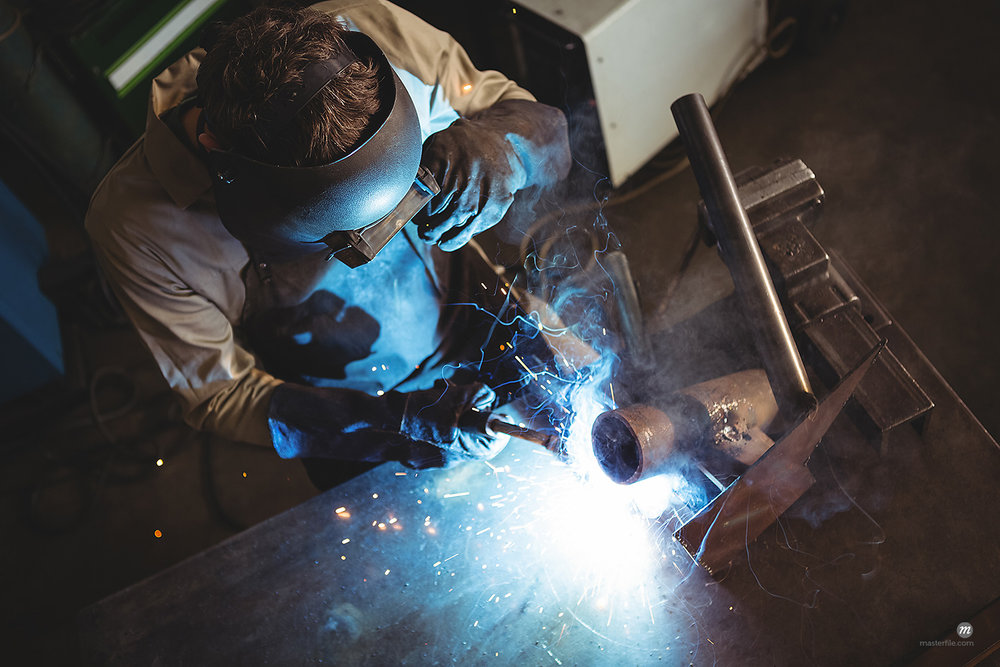 Welder welding a metal in workshop  © Masterfile