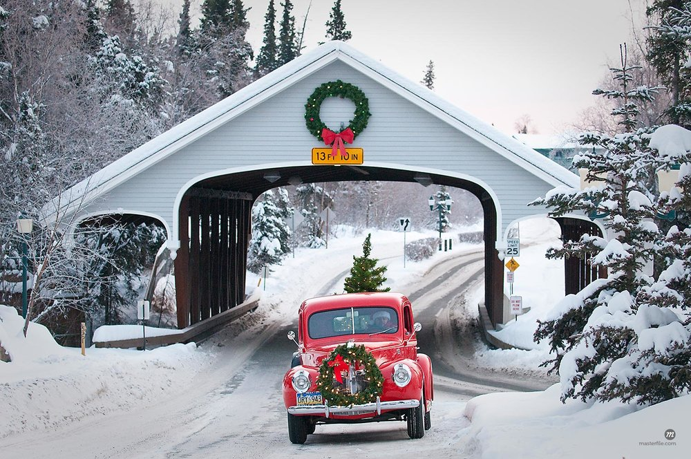 Man driving a vintage 1941 Ford pickup through a covered bridge with a Christmas wreath on the grill and a tree in the back during Winter in Southcentral, Alaska  © AlaskaStock / Masterfile