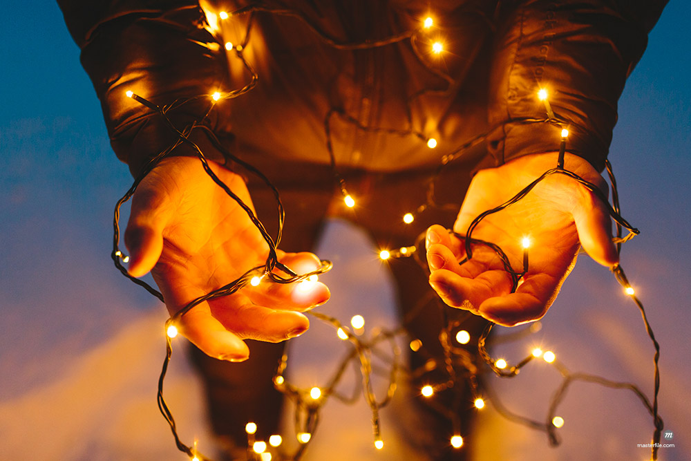 Young man holding Christmas lights  © Masterfile