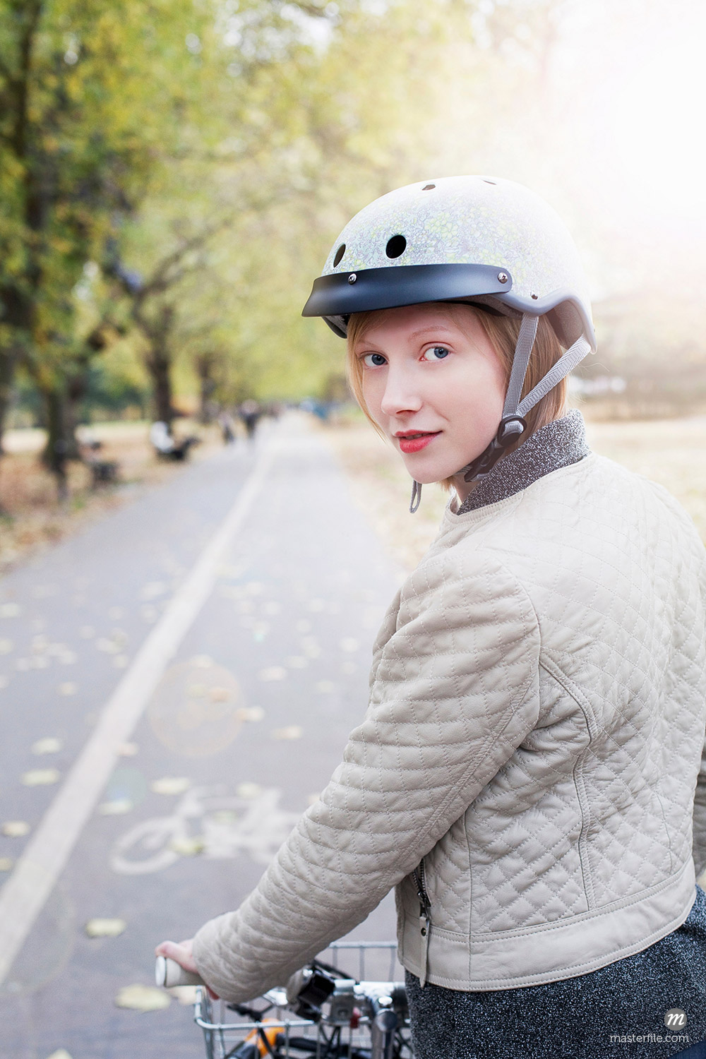 Woman on bicycle in urban park © Masterfile
