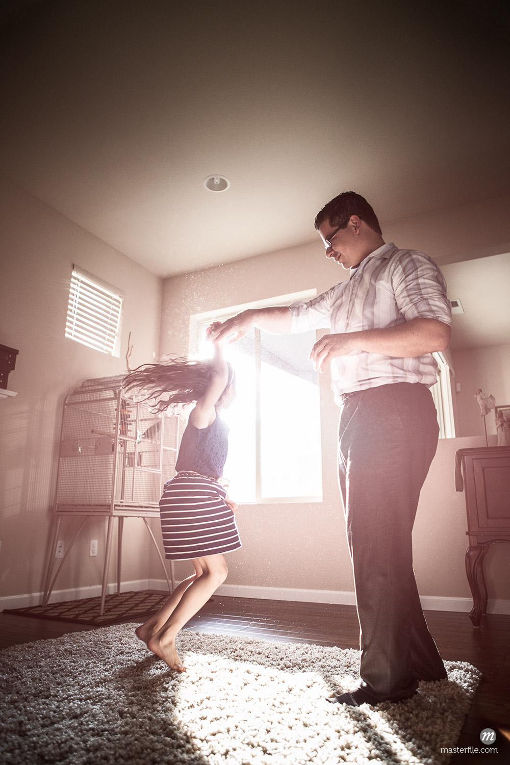 Father and daughter dancing in living room © Blend Images / Masterfile