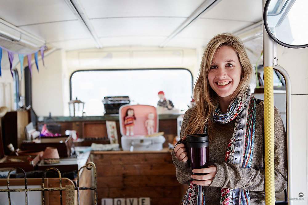A woman standing in a bus converted into a vintage shop at a flea market surrounded by vintage objects  © Masterfile