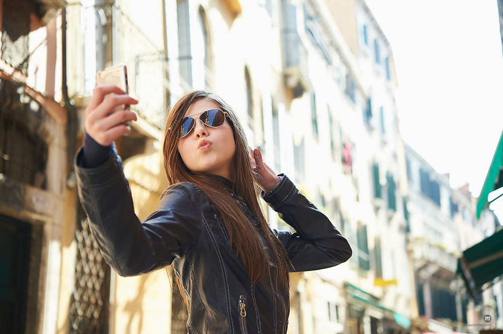 Woman taking selfie with smartphone in Venice, Italy  © Masterfile