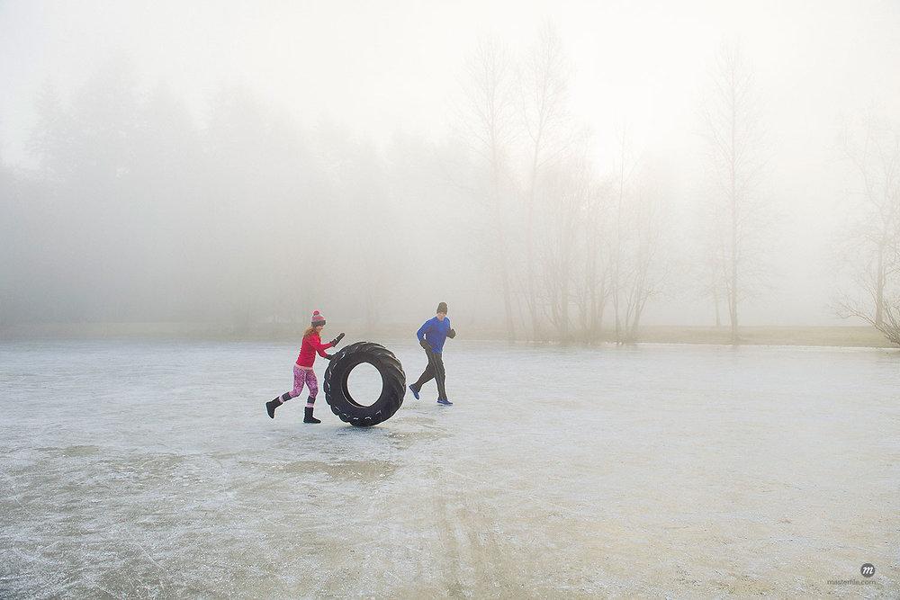 Woman rolling tire across frozen lake  © Masterfile