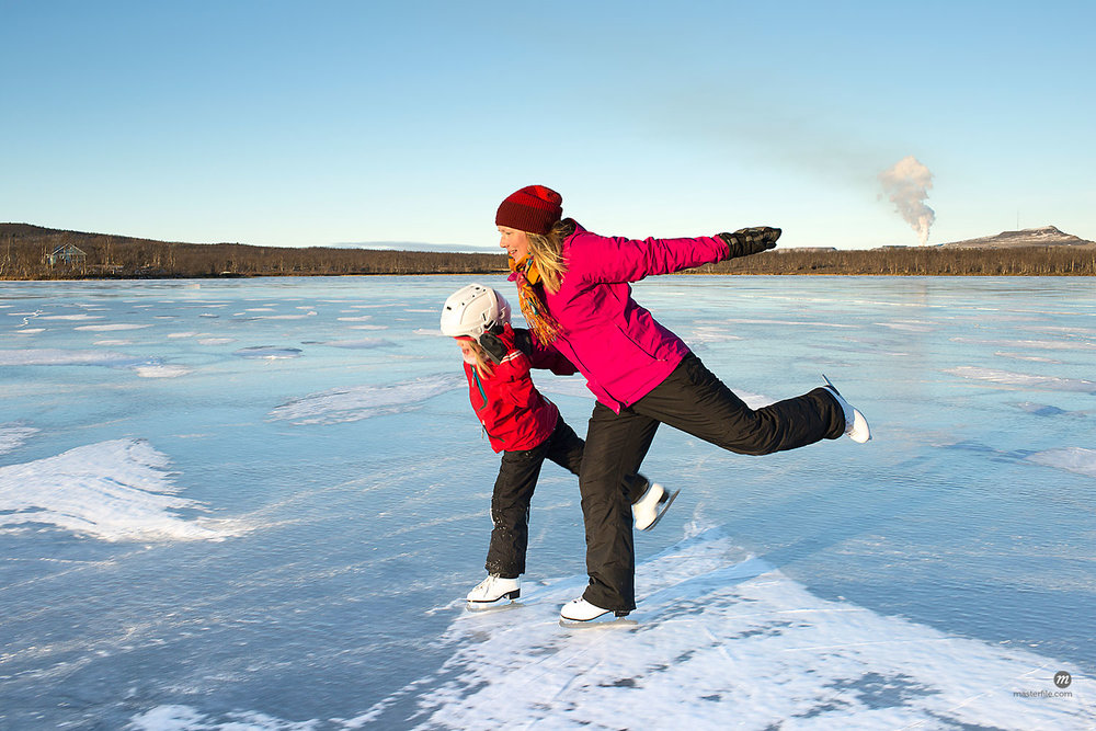 Mother and daughter ice skating on frozen lake © Masterfile