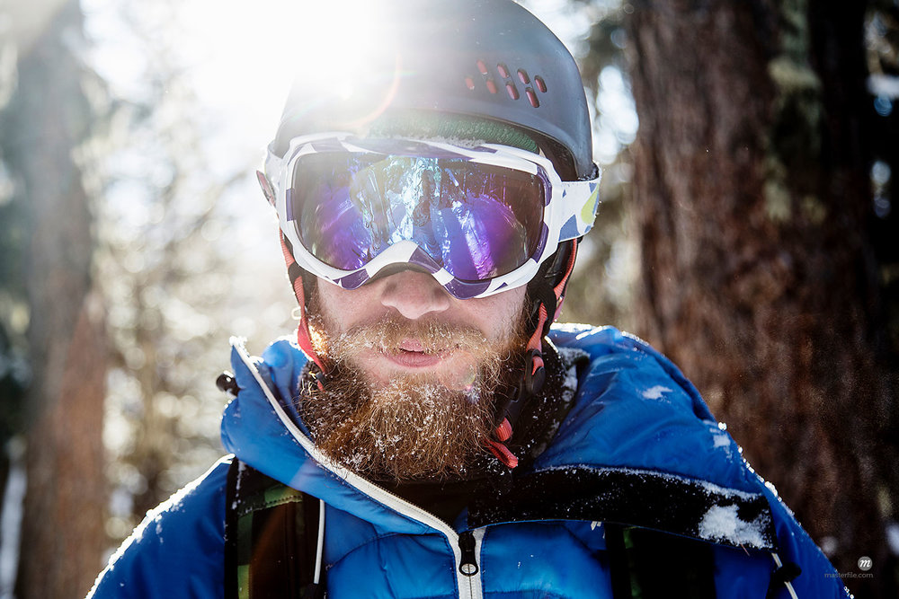 Portrait of male skiier with snow-covered beard and goggles, close-up  © Masterfile