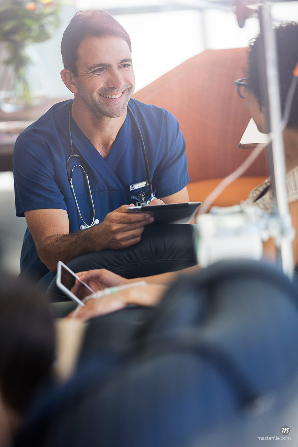 Doctor holding digital tablet, talking to patient © Masterfile