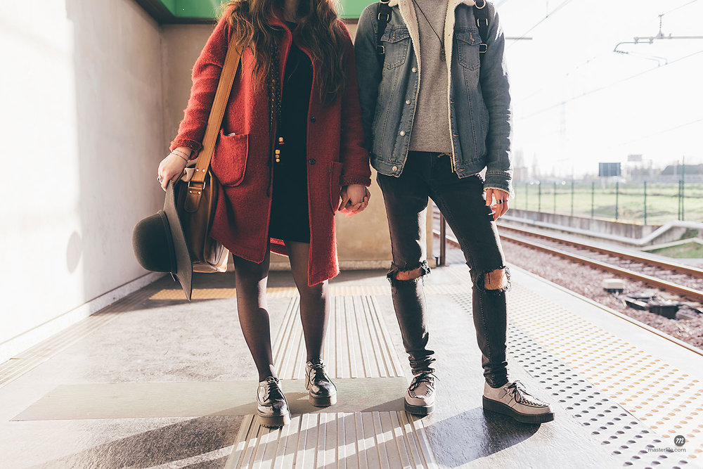 Young couple standing on train platform, low section © Masterfile