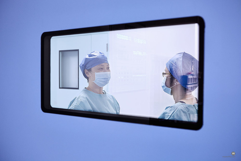 Window view of two female surgeons having discussion in maternity ward operating theatre © Masterfile
