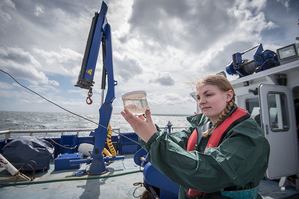 Female scientist inspecting sample of plankton on research ship © Masterfile