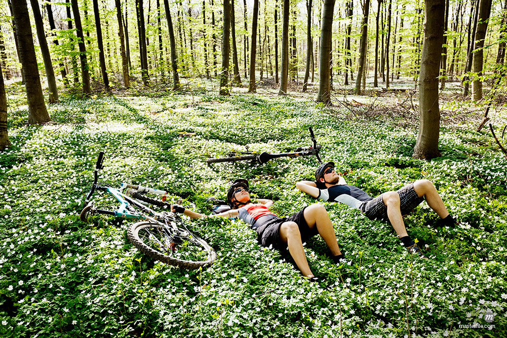 Mountain bikers relaxing in forest © Masterfile