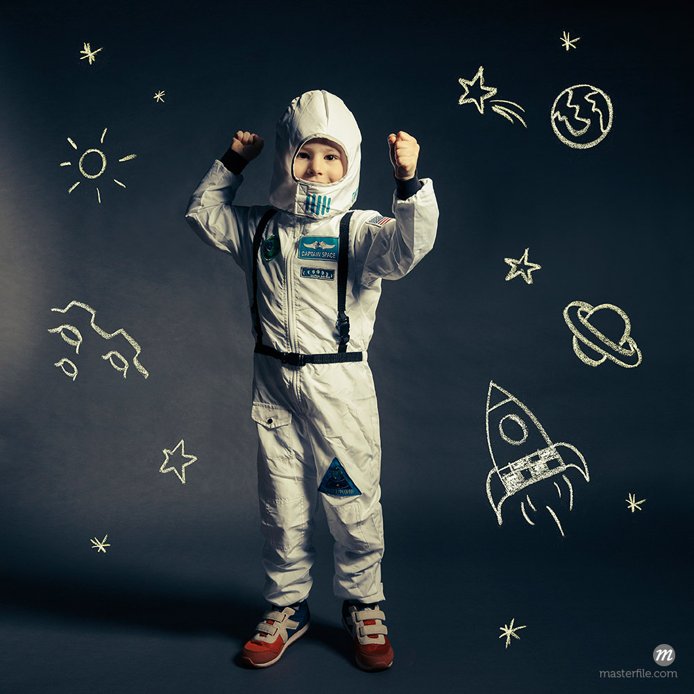 Child with spacesuit orbited by celestial bodies and luminaries © Masterfile