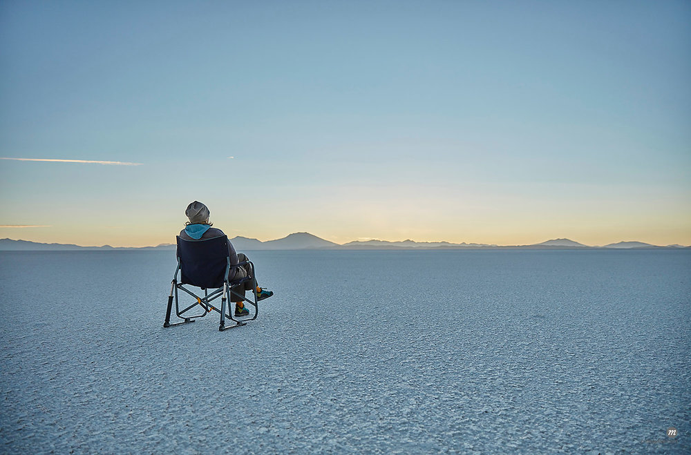 Woman sitting in camping chair, on salt flats, looking at view, Salar de Uyuni, Uyuni, Oruro, Bolivia, South America  © Masterfile