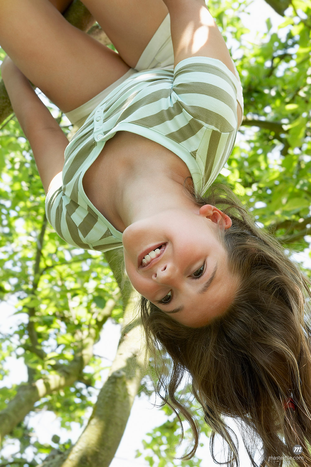 Young girl hanging upside down from tree, low angle view © Masterfile