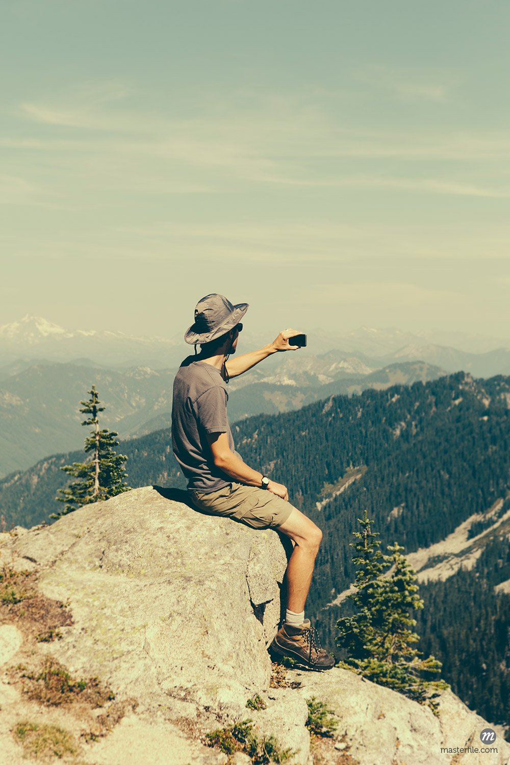 A hiker on a mountain summit, holding a smart phone © Masterfile