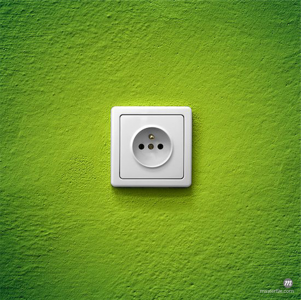 Simple white electric socket on green wall © studio023 / Masterfile