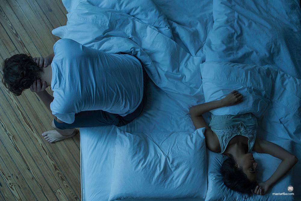Man unable to sleep while wife sleeps comfortably unaware © Masterfile