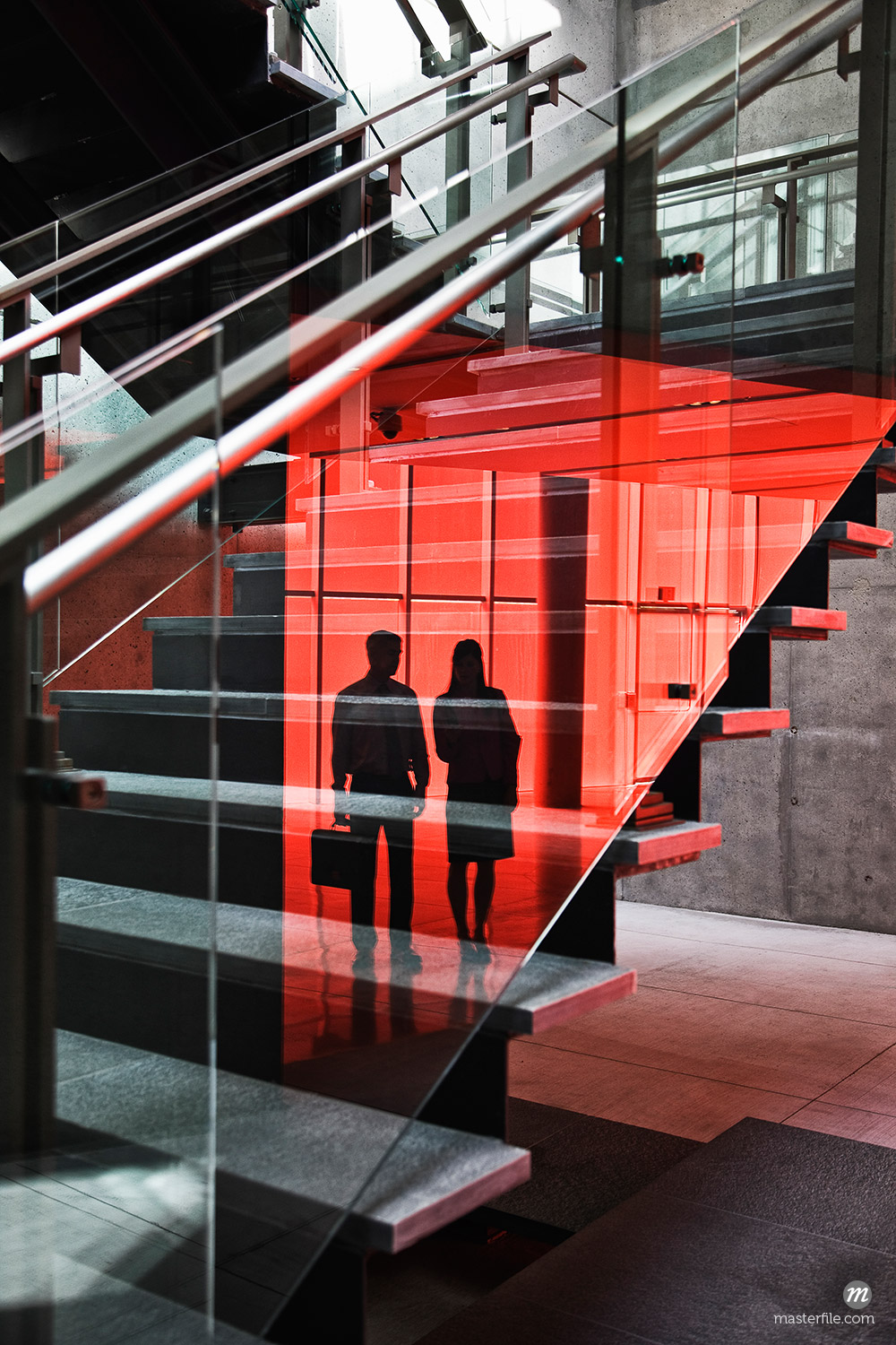 Two businesspeople silhouetted in reflections on the glass around a stairwell of a large office building © Masterfile