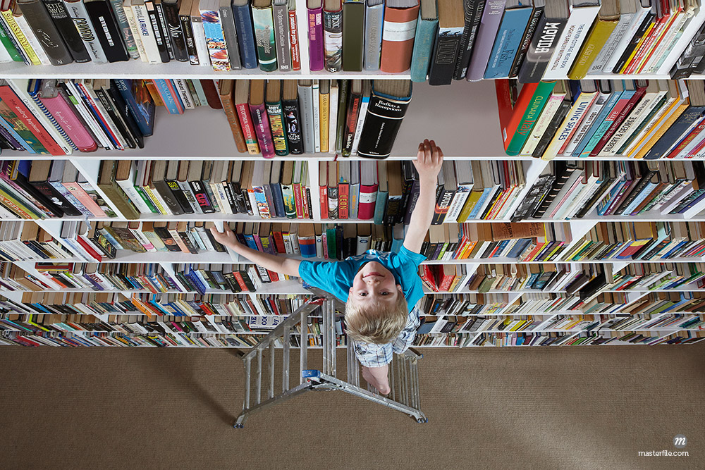 Boy using stepladder on bookshelves © Masterfile