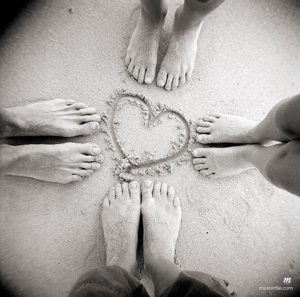 Four pairs of feet standing around a heart shape drawn in sandy beach, Taransay, Outer Hebrides, Scotland © robertharding / Masterfile