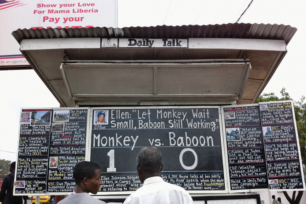 "Bystanders debate the presidential options at the Daily Talk, an English-language news medium, which is published daily on a blackboard on Tubman Boulevard in the center of the Liberian capital, Monrovia.  Liberian president Ellen Johnson Sirleaf's campaign slogan: 'Let monkey wait small, baboon still working"" was referring to the local idiom that monkeys are the hard workers and baboons are lazy, benefiting from all the work the monkeys accomplish."