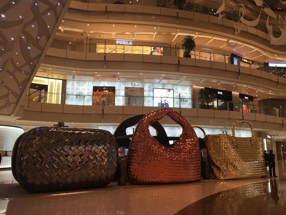 Bottega Veneta larger than life display of purses. You can walk between them. .