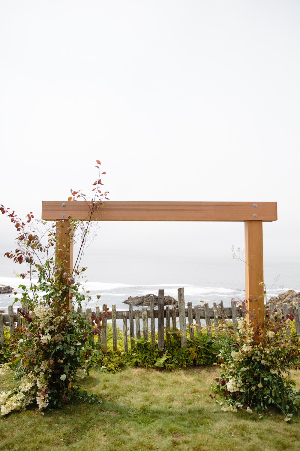 Our architect groom built this arbor, framing the iconic California coast at Sea Ranch.  Photo by Larissa Cleveland.  Event Design by DALD Events.