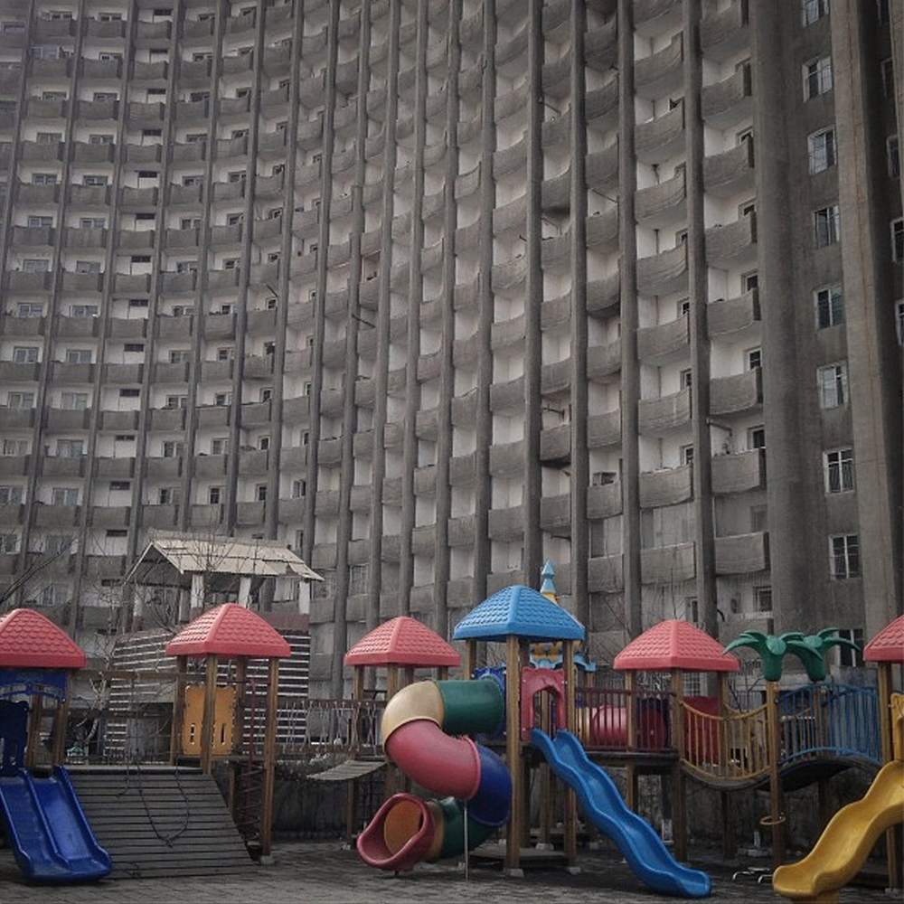 An apartment block stands above the schoolyard playground equipment of a Pyongyang, North Korean kindergarten. Image courtesy of David Guttenfelder.