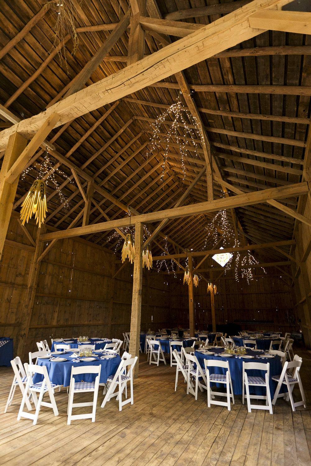 The high, open-beam ceilings of the barn are decorated with lit branches and hand-made chandeliers.   Image by  Ellagraph Studios