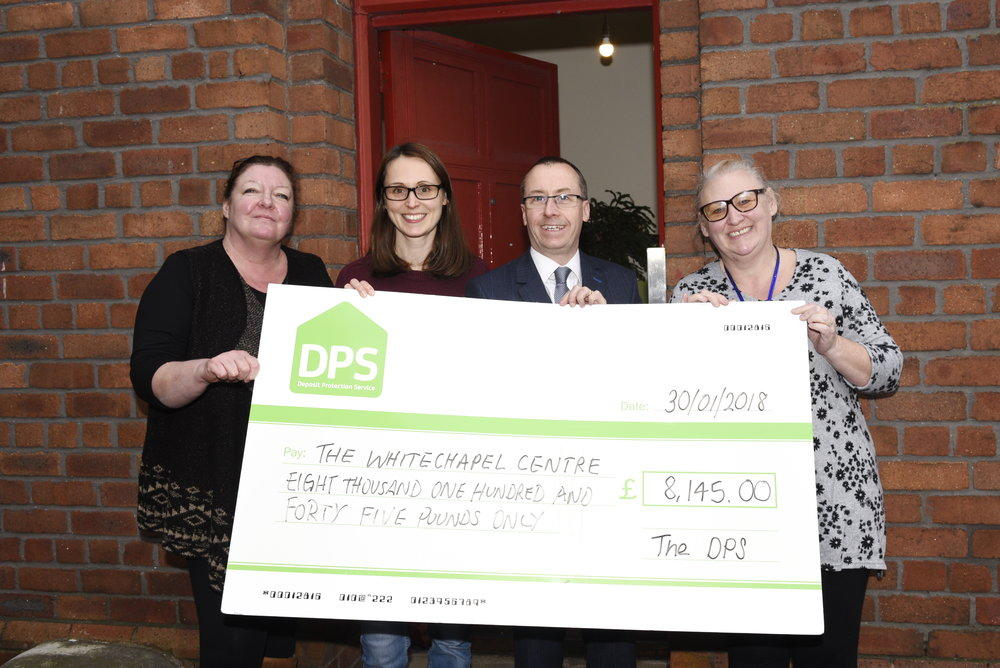Daren King, head of the DPS handing over the funding cheque at the Whitechapel Centre.