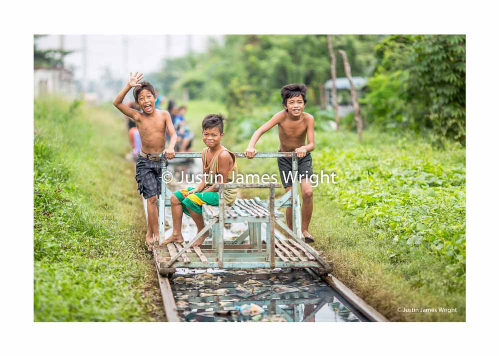 """The Three Musketeers ,  Philippine National Railways, Alabang, Metro Manila, Philippines  Young boys operate a """"trolley"""", a mode of public transportation which runs on the railway tracks in between regular trains"""