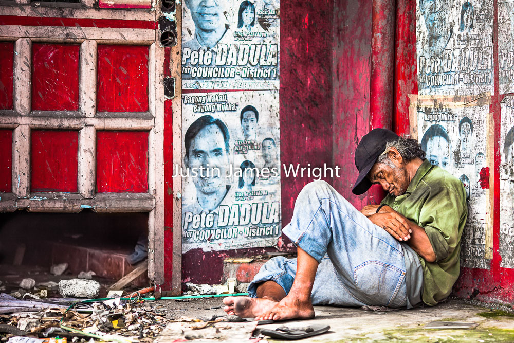A man takes an afternoon rest surrounded by election posters, Makati City, Metro Manila, Philippines   Philippine Image # 4120  If you wish to purchase a photography print of this image, or would like to license this image please contact us using the form below.  Please kindly include the Image Title and Image Ref # in your message, we will get back to you.