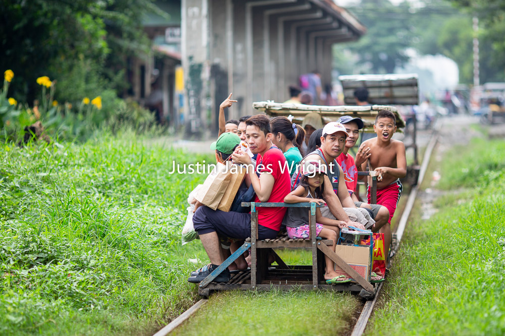 Philippine National Railways (PNR), Alabang Station, Muntinlupa, Philippines   Passengers use a trolley, a mode of public transportation which runs on the railway tracks in between regular trains  Philippine Image # 4111  If you wish to purchase a photography print of this image, or would like to license this image please contact us using the form below.  Please kindly include the Image Title and Image Ref # in your message, we will get back to you.
