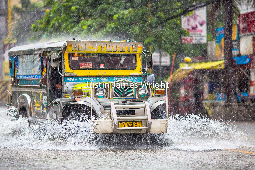 A Jeepney splashes through flood water during a typhoon. Makati City, Philippines