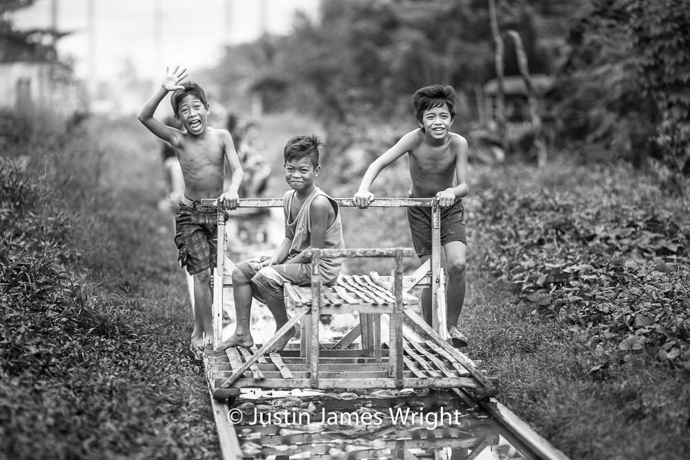 """""""Trolley boys"""" returning to Alabang Station to collect more commuters   Scores of commuters in a city of about 11 million are propelled to their destinations by """"trolley boys"""" pushing makeshift carts that travel a few sections of the sprawling capital's railways.  The resilience of these boys is truly amazing.  Alabang, Muntinlupa, Philippines.  Canon EOS Mk III, EF 135 mm, F 2.0, 1/320 sec."""