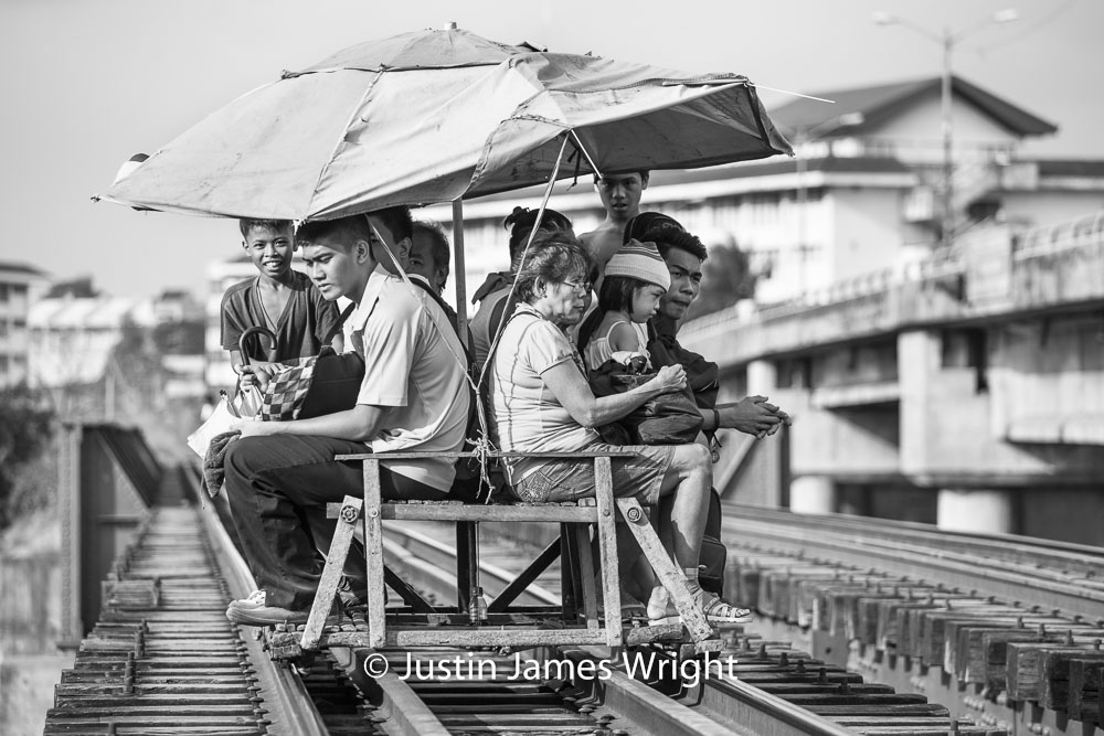 Commuters on aboard a trolley travelling on a bridge crossing the Pasig River   These improvised carts ply the same railway tracks used by the trains of the PNR Metro Commuter Line.  Pandacan, Manila, Philippines.  Canon EOS Mk III, EF 70 - 200 mm, F 4.0, 1/500 sec.