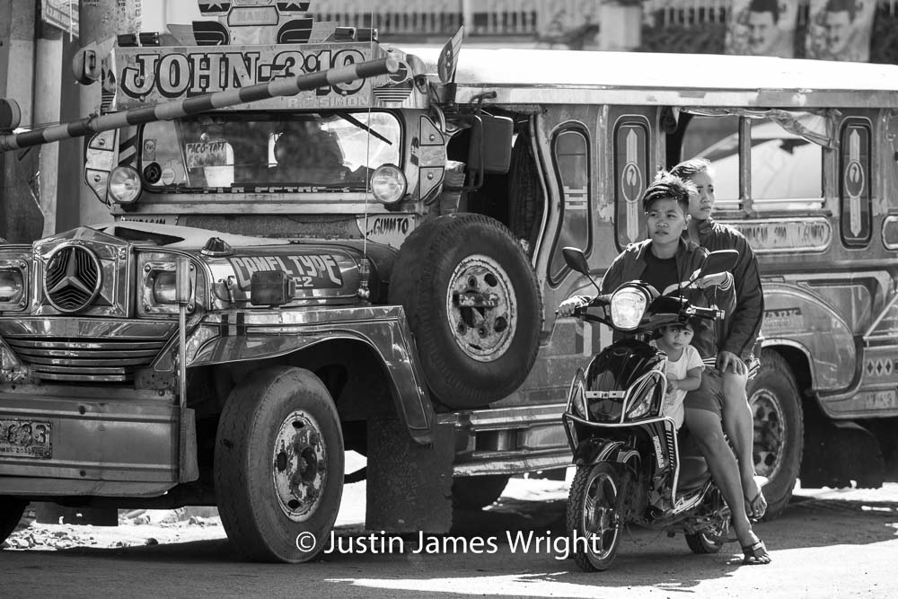 A passenger jeepney and motorcycle wait at a level crossing for a train to pass   Pandacan, Manila, Philippines.  Canon EOS Mk III, EF 70 - 200 mm, F 4.0, 1/500 sec.