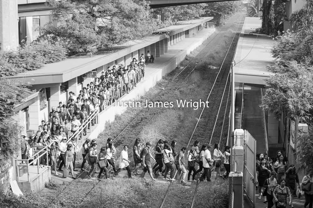 Commuters cross the railway tracks to exit Edsa station   Makati City, Metro Manila, Philippines.  Canon EOS Mk III, EF 70 - 200 mm, F 4.0, 1/400 sec.