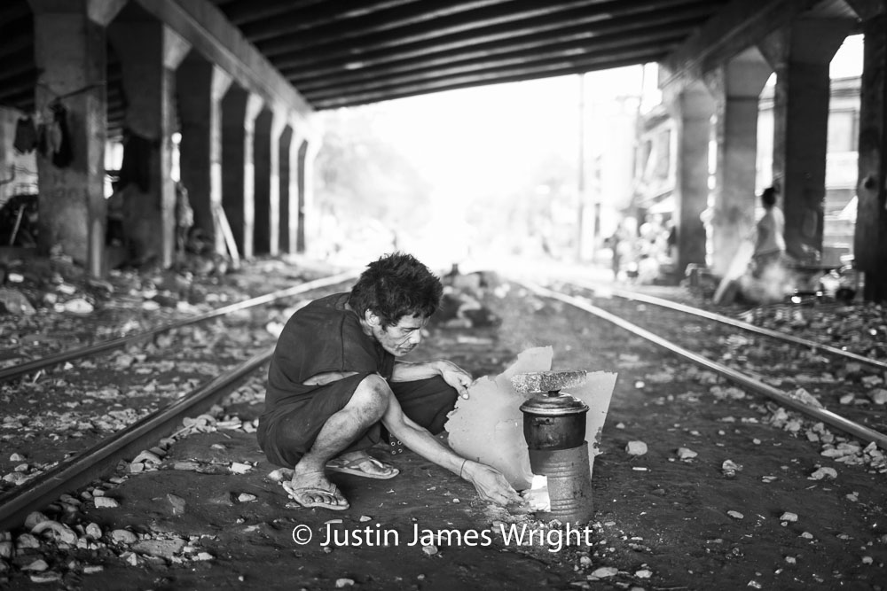 Cooking between the railway tracks   Sta Mesa, Manila, Philippines.  Canon EOS Mk III, EF 35 mm, F 1.4, 1/125 sec.