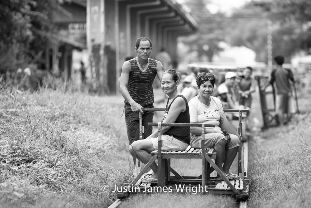 Commuters depart Alabang railway station on board a trolley   Homemade wooden carts take Filipinos to work or school without the hassles of traffic and at a cheaper price.  Alabang, Muntinlupa, Philippines.  Canon EOS Mk III, EF 135 mm, F 2.0, 1/320 sec.