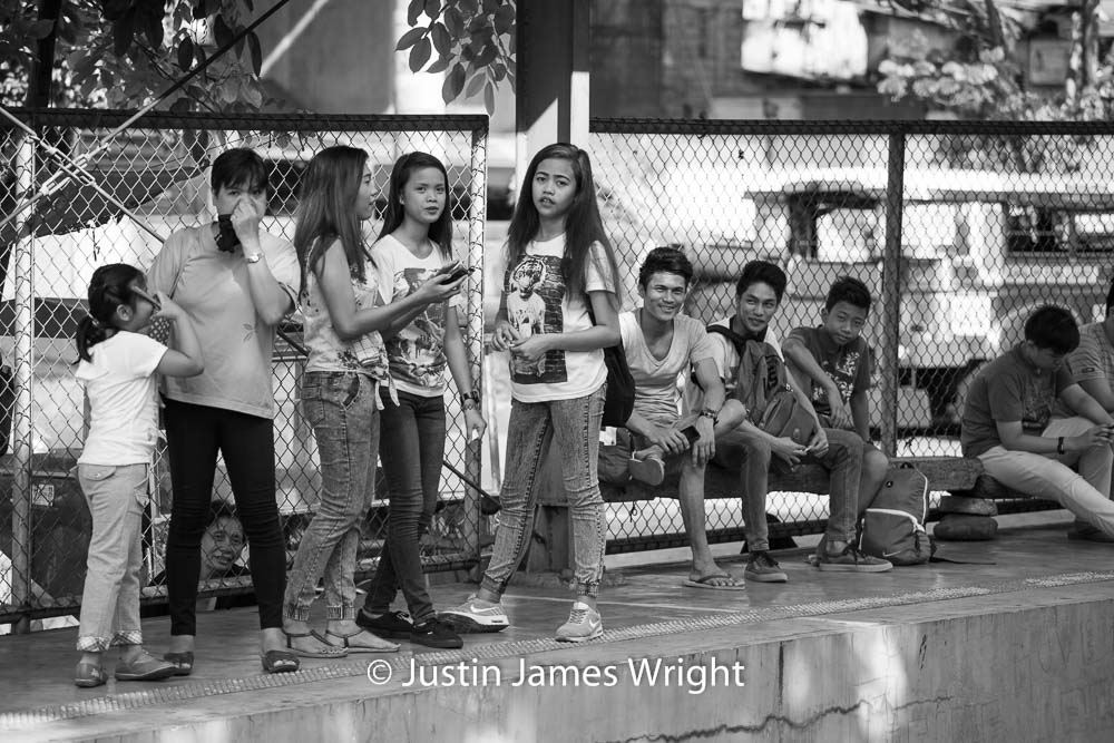 Commuters waiting for a train at San Andres station   Makati City, Metro Manila, Philippines.  Canon EOS Mk III, EF 70 - 200 mm, F 4.0, 1/400 sec.